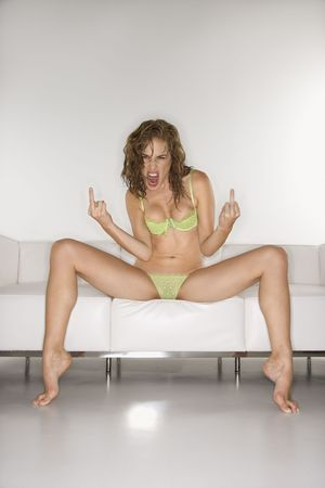 bold: Sexy Caucasian mid-adult woman in underwear sitting on couch with legs apart making obscene gesture at viewer.
