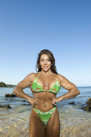 Pretty Caucasian mid adult woman bodybuilder in bikini flexing muscles on Maui beach. photo