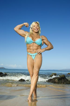 Pretty Caucasian mid adult woman bodybuilder in bikini flexing bicep on Maui beach.