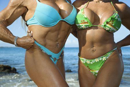 navel piercing: Close up torsos of Caucasian mid adult women bodybuilders in bikinis standing on Maui beach. Stock Photo