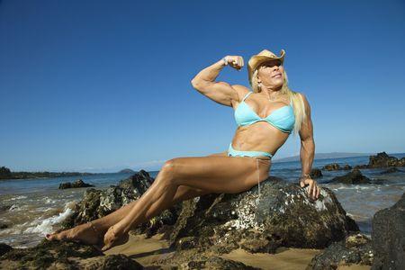 Pretty Caucasian mid adult woman bodybuilder in bikini sitting on rock flexing bicep on Maui beach. photo