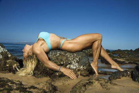 Pretty Caucasian mid adult woman bodybuilder in bikini lying on rock on Maui beach. photo