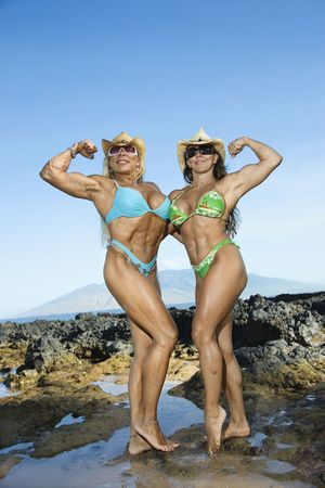 Pretty Caucasian mid adult women bodybuilders in bikinis standing and flexing  biceps on Maui beach. photo