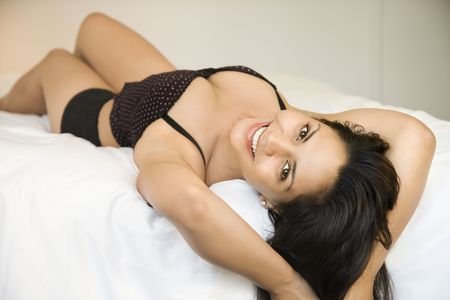 Hispanic young adult woman lying on bed wearing lingerie and looking at viewer. Stock Photo