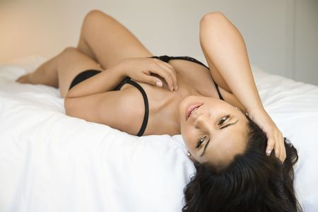 Hispanic young adult woman in lingerie lying on bed with hand in hair. photo