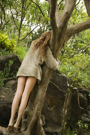 Back view of Caucasian young adult woman wearing only a sweater hugging a tree.
