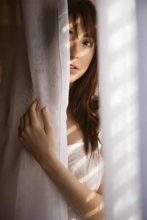 half length posed: Portrait of pretty Caucasian young woman standing in sunlit curtains. Stock Photo