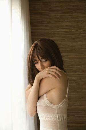 Portrait of pretty Caucasian young woman by sunlit window.