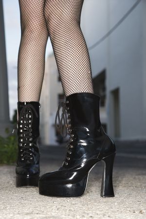 high heeled: Legs and feet wearing high heeled boots of Caucasian young woman in urban setting. Stock Photo