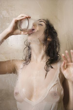 wet breast: Pretty Caucasian young woman wet in shower in transparent shirt drinking glass of water.