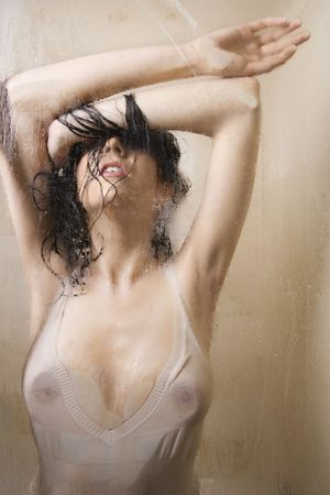 wet breast: Pretty Caucasian young woman wet in shower in transparent shirt leaning against glass.