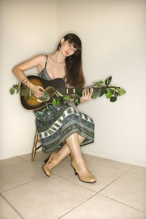 Young adult Caucasian woman sitting playing guitar. photo