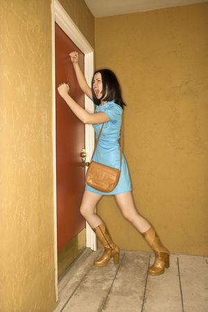 Caucasian young adult woman in retro clothing pounding fists on door and yelling. Stock Photo