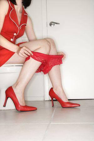 bathroom women: Caucasian young adult woman sitting on toilet holding underwear around legs. Stock Photo