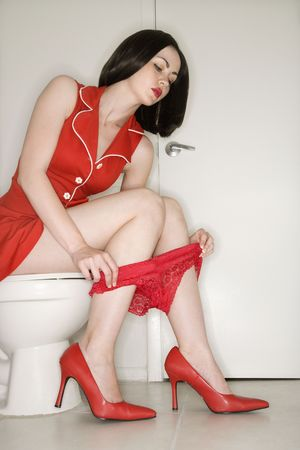 Caucasian young adult woman sitting on toilet holding underwear around legs. Stock Photo