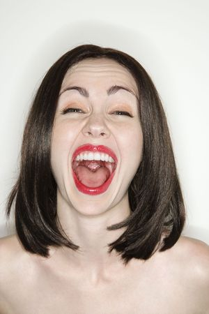 scream: Caucasian young adult woman making facial expression at viewer.