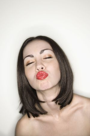 puckering lips: Caucasian young adult  woman puckering lips at viewer. Stock Photo