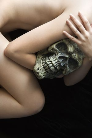Caucasian young adult woman lying down holding human skull. photo