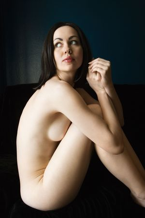 Nude young adult Caucasian woman sitting and looking over her shoulder.
