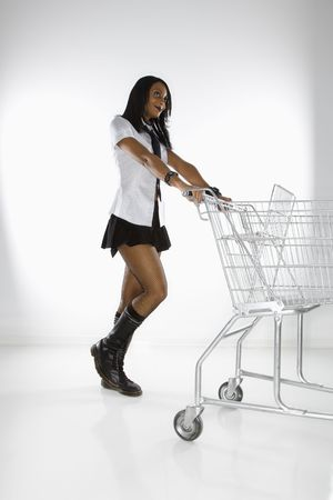Mid-adult African American woman in mini skirt and boots pushing shopping cart. photo