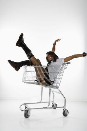 mini falda: Mediados de adultos African American mujer en mini falda y botas sentado en el carrito de compra con los brazos y las piernas.
