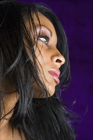 african american woman: Portrait of mid-adult African American woman against purple background.