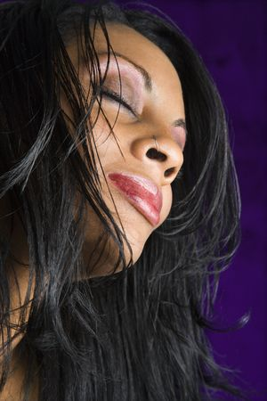Portrait of mid-adult African American woman against purple background.  photo