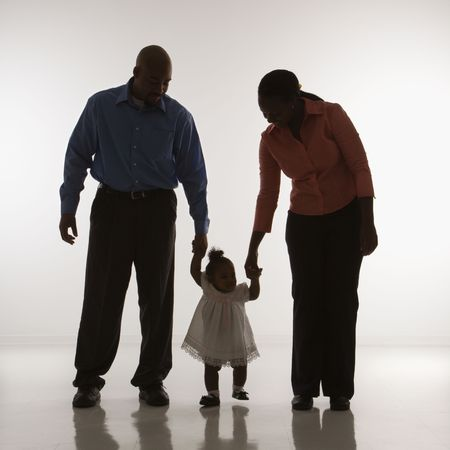 holding close: African American man and woman standing holding up infant girl by her hands against white background.