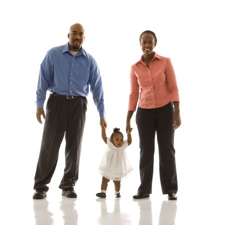 African American man and woman standing holding up infant girl by her hands against white background. photo