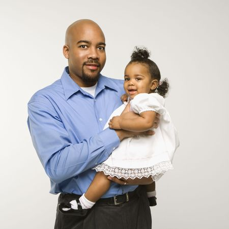 African American man holding infant girl standing against white background. Stock Photo - 2204912