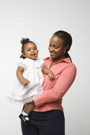 african american infant: African American woman holding infant girl standing against white background. Stock Photo