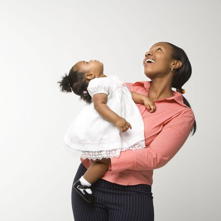 African American woman holding infant girl standing against white background. Stock Photo