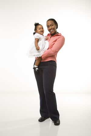 African American woman holding infant girl standing against white background. Stock Photo - 2204779