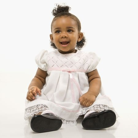 african american infant: Portrait of African American infant girl sitting against white background.