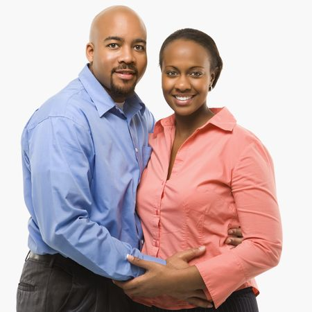 couple embracing: Portrait of African American couple with arms around eachother against white background.