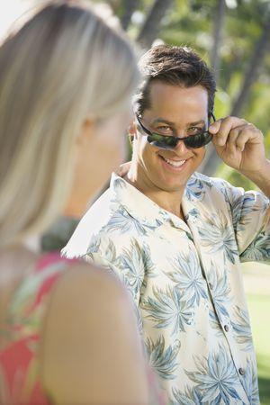 mid adult man: Hombre mediados de cauc�sico del adulto que inclina las gafas de sol en la mujer.