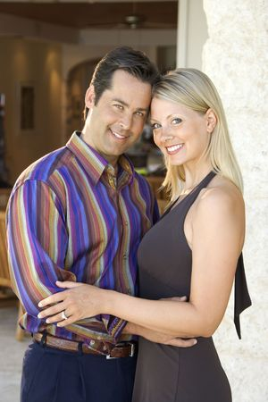 mid adult couple: Caucasian mid adult couple embracing and smiling at viewer.