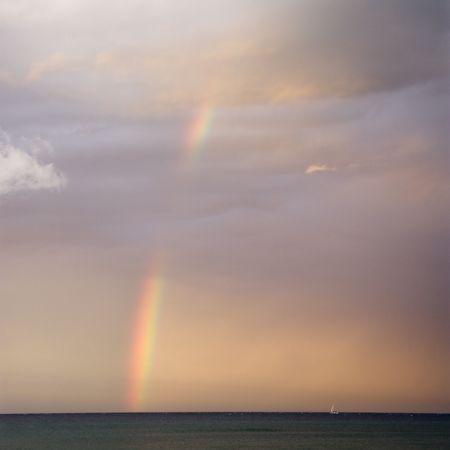 Rainbow spreading across sky on coast in Maui Hawaii. photo