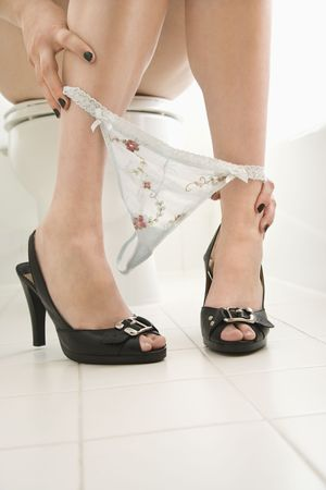 Caucasian young adult female sitting on toilet with underwear around ankles and high heels.