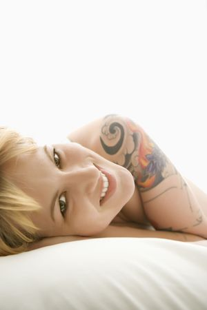 Caucasian young adult woman lying on bed smiling at viewer. photo