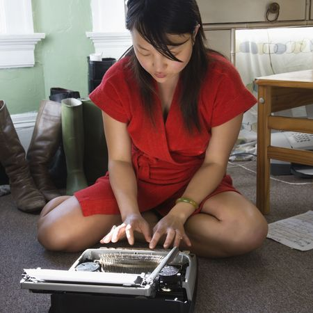 Pretty Asian young woman sitting on floor in red robe typing on typewriter. photo
