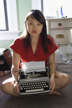 Pretty Asian young woman sitting on floor in red robe holding typewriter. photo