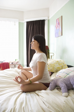 Side view of pretty  Asian young woman sitting on bed in underwear and t-shirt meditating in lotus pose. Stock Photo - 2205202