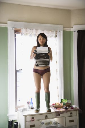 Pretty young Asian woman in underwear and rubber boots holding typewriter. photo
