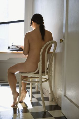 Back view of nude young Asian woman sitting at kitchen table typing on typewriter.