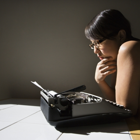 young Asian woman sitting at kitchen table reading paper in typewriter. Stock Photo - 2205533