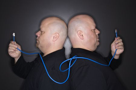 Caucasian bald mid adult identical twin men standing back to back holding ethernet cable.