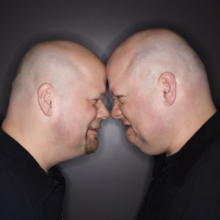 Caucasian bald mid adult identical twin men standing face to face with angry expression. photo