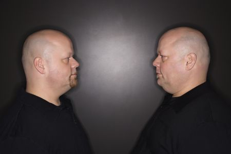 kinship: Caucasian bald mid adult identical twin men standing face to face staring. Stock Photo