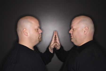 kinship: Caucasian bald mid adult identical twin men standing face to face with hands touching.